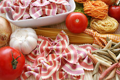 Italian pasta. Some raw mixed italian pasta and tomatoes Stock Photography