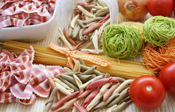 Italian pasta. Some raw mixed italian pasta and tomatoes Royalty Free Stock Image