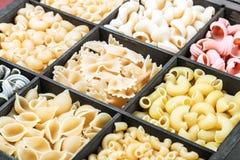 Italian pasta assortment. Pasta assortment background. Pasta in a wooden box. Italian pasta of different colors Stock Images