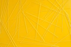 Italian pasta background. Spaghetti pasta is scattered on a yellow background. Top view, flat lay Royalty Free Stock Photos