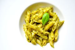 Italian pasta with basil pesto on a white plate. Typical italian vegetarian dish Stock Photo