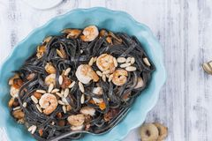 Italian Pasta is black with mussels and shrimps. Parmesan, Seafood, various snacks for dinner. Bright dishes and white background royalty free stock images