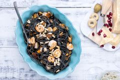 Italian Pasta is black with mussels and shrimps. Parmesan, Seafood, various snacks for dinner. Bright dishes and white background stock image