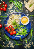 Italian pasta in bowl with tomatoes and ingredients for cooking, top view. Royalty Free Stock Image