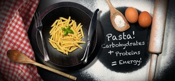 Italian Pasta - Carbohydrates Proteins Energy. Traditional raw food called Penne or macaroni, Italian pasta in a wooden dish on a table with kitchen utensils royalty free stock images