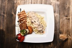 Italian pasta with chicken and mushrooms near grilled croutons and tomato as decor, wooden backgroun stock images