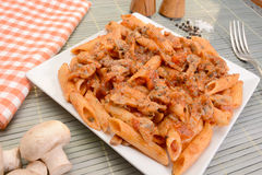 Italian pasta closeup. Penne pasta with tomato, mushrooms and basil - closeup Royalty Free Stock Images