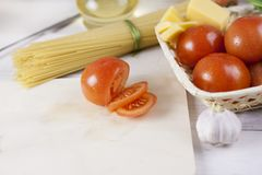 Italian pasta Cooking Still Life. Dry spaghetti or macaroni, oliv oil, tomatoes, green and cheese on wooden kitchen table. Selecti. Ve focus. Copy space Stock Photos