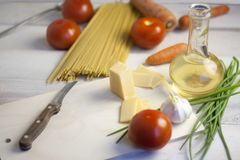 Italian pasta Cooking Still Life. Dry spaghetti or macaroni, oliv oil, tomatoes, green and cheese on wooden kitchen table. Selecti. Ve focus Stock Photos