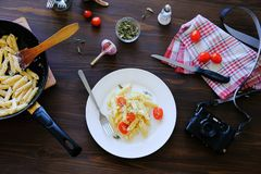 Italian pasta with cream sauce, cheese, tomatoes and spices on a white plate and in a pan on a wooden table. Lying next to the stock images