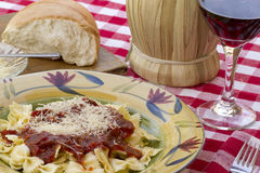 Italian Pasta Dinner Served with Wine and Bread. Italian pasta dinner served with Marinara sauce, parmesan cheese, over bow tie noodles accompanied by a glass of Stock Photos