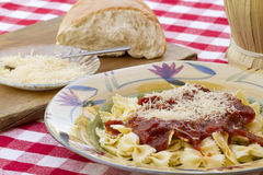 Italian Pasta Dinner Served with Wine and Bread. Italian pasta dinner served with Marinara sauce, parmesan cheese, over bow tie noodles accompanied by a glass of Royalty Free Stock Images