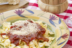 Italian Pasta Dinner Served with Wine and Bread. Italian pasta dinner served with Marinara sauce, parmesan cheese, over bow tie noodles accompanied by a glass of Stock Photo