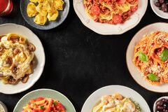Free Italian Pasta Dishes Forming A Frame For Copy Space, Overhead Shot On A Dark Background. Pastas With Meat, Vegetables, Seafood, Royalty Free Stock Image - 200855416
