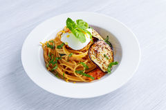 Italian Pasta with eggplants, tomato, ricotta cheese and basil Stock Photos