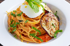 Italian Pasta with eggplants, tomato, ricotta cheese and basil Stock Photo