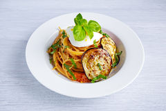 Italian Pasta with eggplants, tomato, ricotta cheese and basil Stock Photography