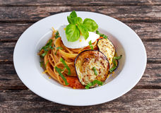 Italian Pasta with eggplants, tomato, ricotta cheese and basil Stock Images