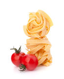 Italian pasta fettuccine nest  and cherry tomato Royalty Free Stock Images