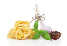 Italian pasta fettuccine nest with garlic and fresh basil leaves Stock Photos