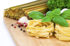 Italian pasta fettuccine nest with garlic and fresh basil leaves Royalty Free Stock Photo