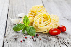 Italian pasta fettuccine nest with garlic, tomatoes basil Stock Photo