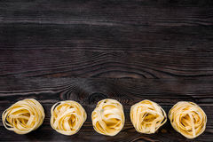 Italian pasta fettuccine nest on grey wooden table top view copyspace.  Stock Images