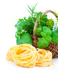 Italian pasta fettuccine nest with wicker basket green herbs Royalty Free Stock Photography