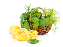Italian pasta fettuccine nest with wicker basket green herbs Stock Photos