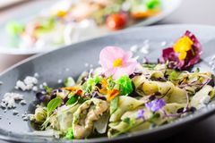 Italian pasta fettucine with chicken pieces and flowers decoration.  royalty free stock images