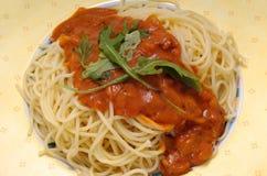 Italian pasta food. Spaghetti Napolitana with ruccola salad stock image