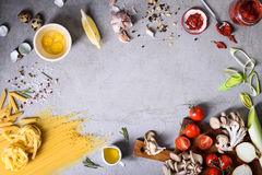 Italian pasta food frame, Spaghetti, linguine and penne with ingredients over grey concrete background. Top view, copy space,. Flat lay Stock Image