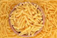 Italian pasta fusilli in a wooden bowl Stock Images