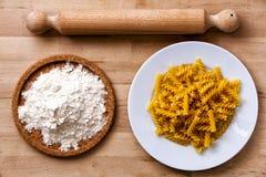 Italian pasta, fusilli. Rolling pin, flour. Wooden surface. Stock Photos