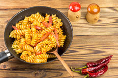 Italian pasta fusilli with tomato sauce and sausage in pan, wooden spoon, red pepper on table, top view, space for text Royalty Free Stock Images