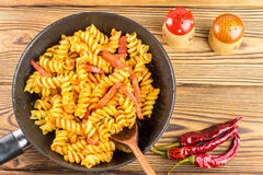 Italian pasta fusilli with tomato sauce and sausage in pan, wooden spoon, red pepper on table, top view, space for text Stock Photos