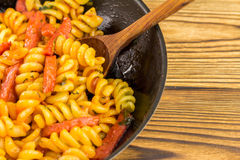 Italian pasta fusilli with tomato sauce and sausage in pan, wooden spoon on table, space for text Royalty Free Stock Photography