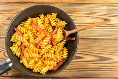 Italian pasta fusilli with tomato sauce and sausage in pan, wooden spoon on table, top view, space for text Royalty Free Stock Images
