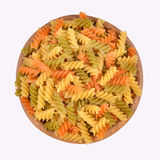 Italian pasta fusilli in a wooden bowl. On a white background Royalty Free Stock Photo