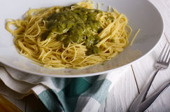 Italian pasta with green pesto on wood background Royalty Free Stock Images
