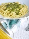 Italian pasta with green pesto on wood background Stock Image