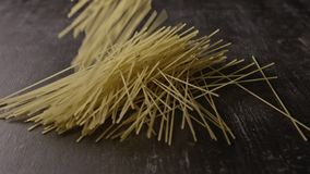 Italian pasta homemade are falling on a dark wooden background. Slow motion, Full HD video, 240fps, 1080p. Italian pasta, spaghetti, falling in slow motion on a stock video footage