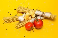 Italian pasta ingredients on a yellow background, top view stock photo