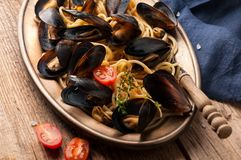 Italian pasta with mussels in black shells and cut tomatoes in metal golden plate stock photo