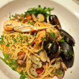 Italian pasta with mussels. Pasta with mussels, lobster and parsley in brine. Prepared in Italy with fresh tomatos, garlic, herbs.. Presented on a white plate royalty free stock photos