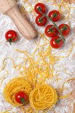Italian pasta nest egg, cherry tomatoes and rolling pin Stock Photography
