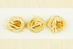 Italian pasta nest. Over white background royalty free stock photography