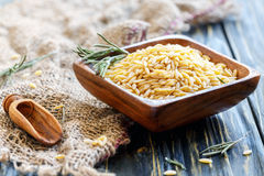 Italian pasta orzo in a wooden bowl. Stock Images