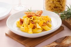 Italian pasta, penne with bacon and pumpkin. Horizontal setting Royalty Free Stock Image