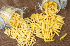 Italian pasta - penne and fusilli in glass jar Royalty Free Stock Photo